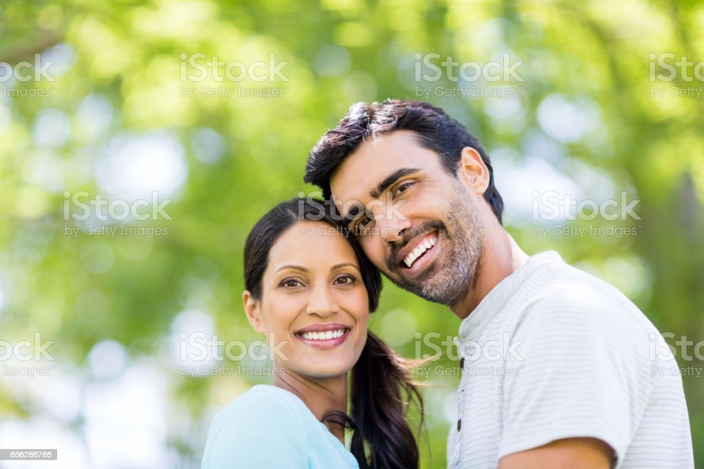 Portrait of couple embracing each other in park stock photo