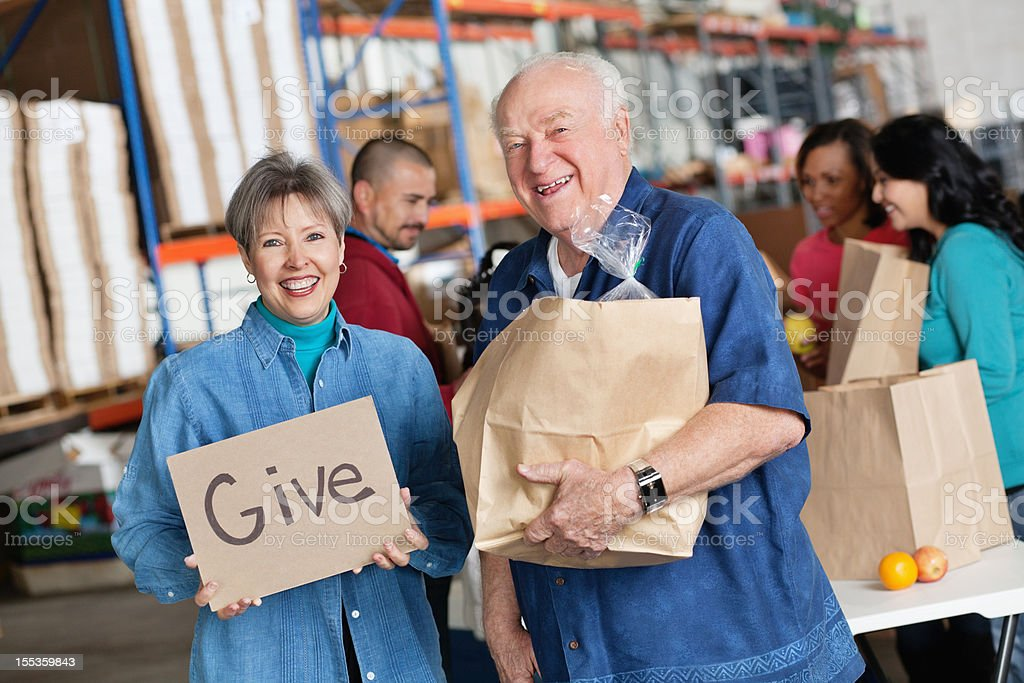 Portrait of couple promoting giving at a food bank royalty-free stock photo