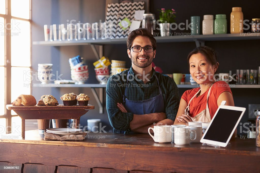 Portrait Of Couple Running Coffee Shop Behind Counter stock photo