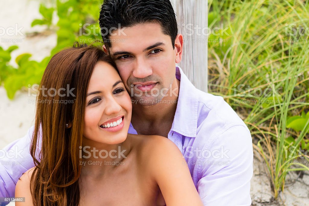 Portrait of couple sitting in a park as girlfriend smiles stock photo