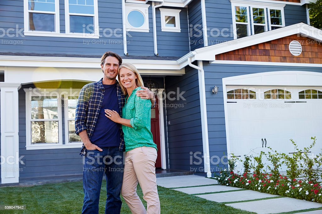 Portrait Of Couple Standing Outside House stock photo