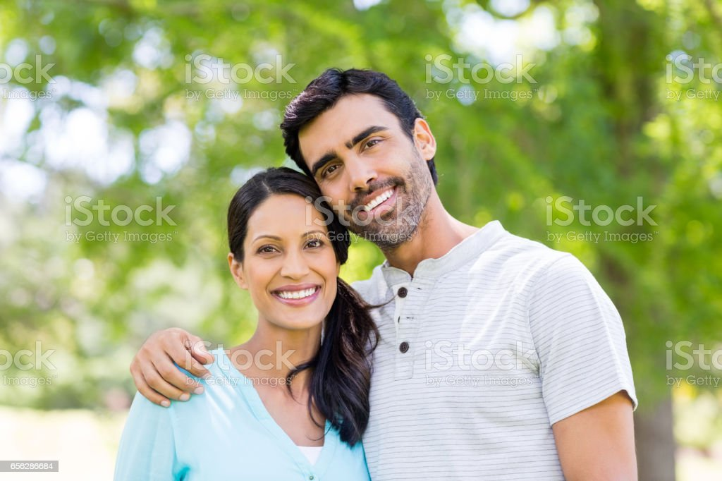 Portrait of couple standing together in park stock photo