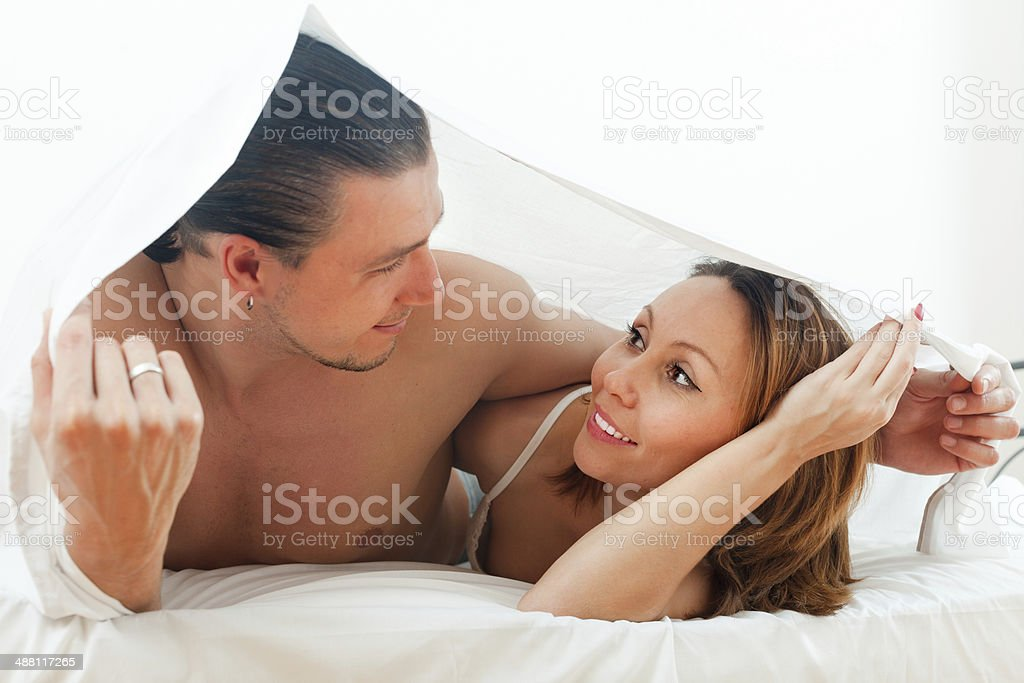 Portrait of  couple  together under sheet stock photo