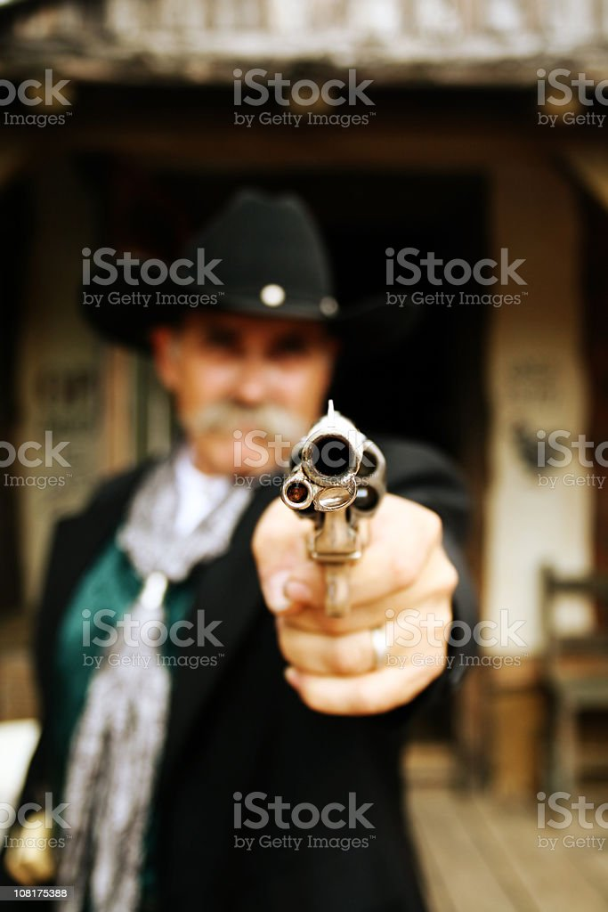 Portrait of Cowboy Holding Gun Up stock photo