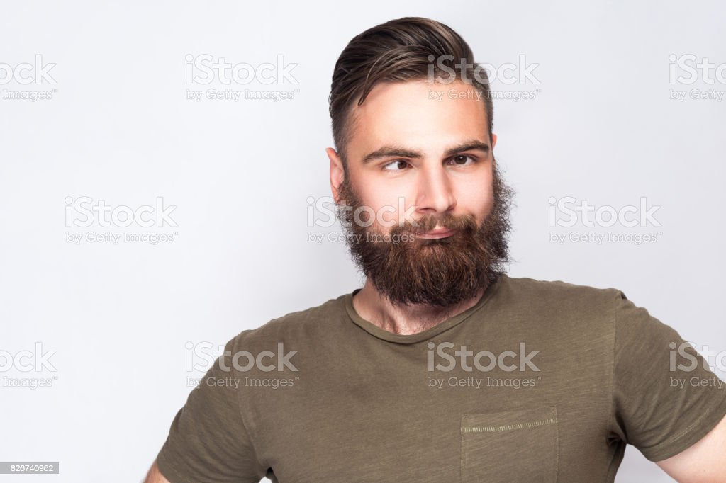 Portrait of crazy cross eyed bearded man with dark green t shirt against light gray background. stock photo