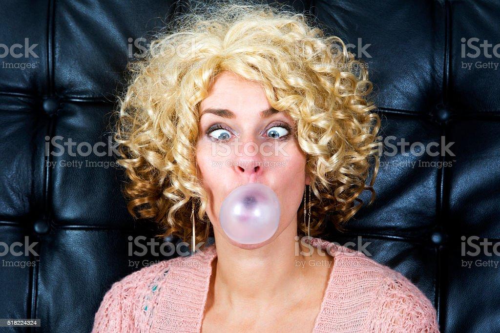 portrait of cross-eyed blond woman with bubblegum stock photo