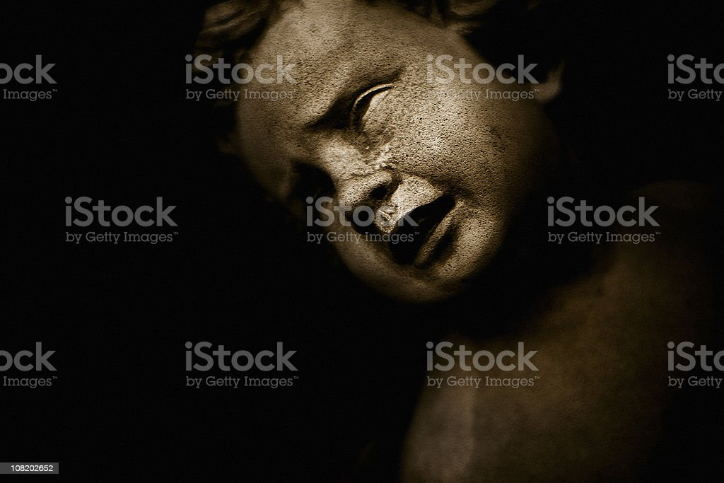 Portrait of Crying Stone Child Statue, Low Key royalty-free stock photo