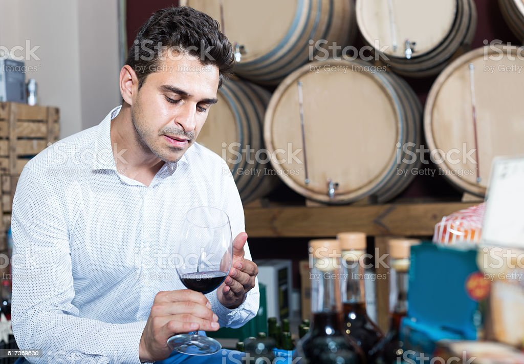 Portrait of customer holding glass of red wine in shop stock photo