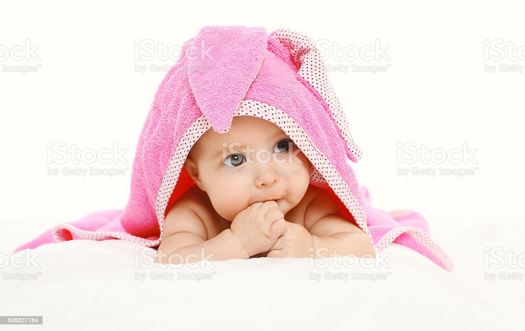 Portrait of cute baby under towel lying on bed stock photo