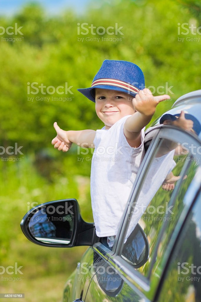 Portrait of cute boy in car showing thumbs up sign royalty-free stock photo