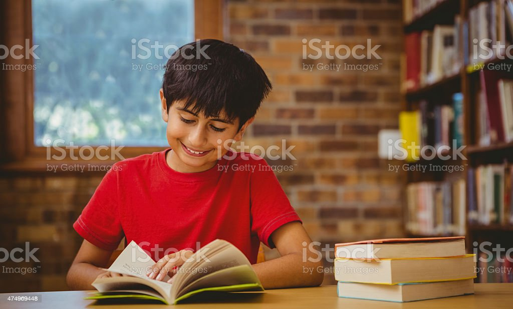 Portrait of cute boy reading book in library stock photo