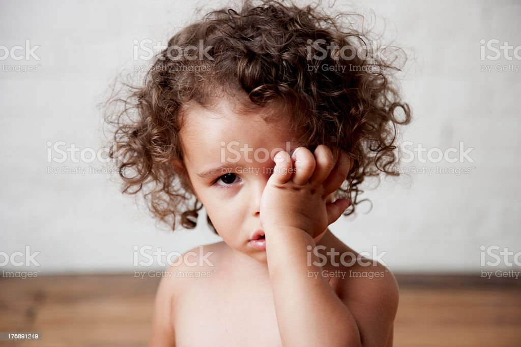Portrait of cute crying toddle girl rubbing her eye stock photo