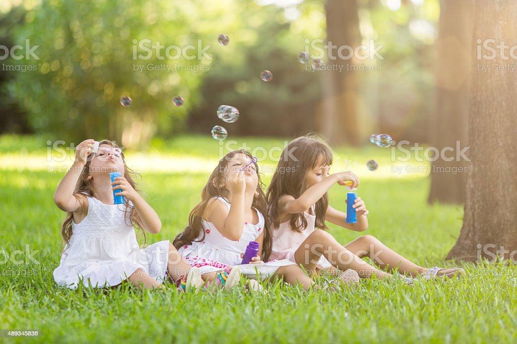 Portrait of cute friends having bubble fun on green lawn stock photo