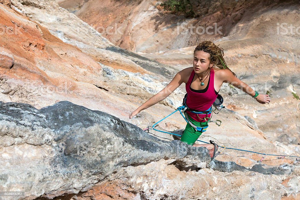 Portrait of Cute Girl rock Climber hanging vertical orange wall stock photo