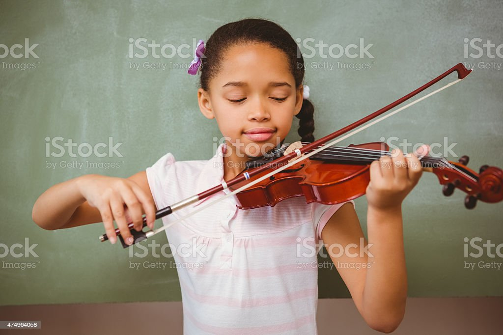 Portrait of cute little girl playing violin stock photo