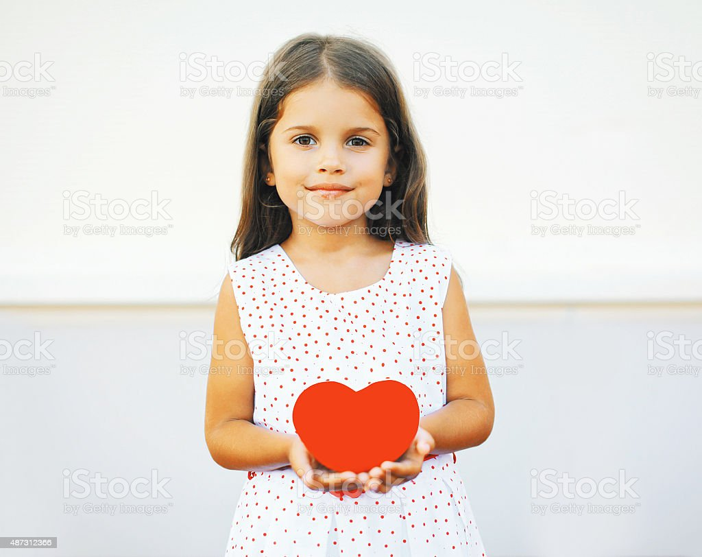 Portrait of cute little girl with red paper heart stock photo