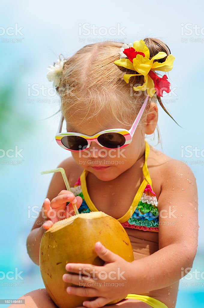 portrait of cute toddler girl with coconut cocktail stock photo