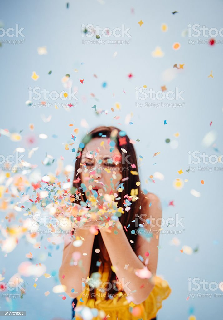 Portrait of  cute woman blowing confetti at holiday party stock photo