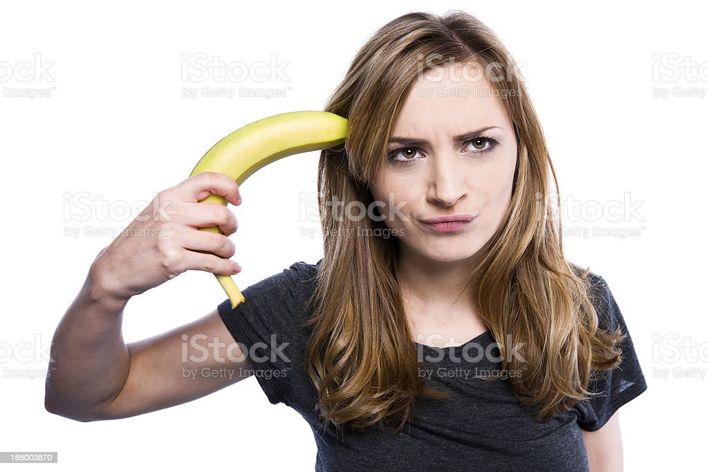Portrait of cute woman pointing banana to her head stock photo