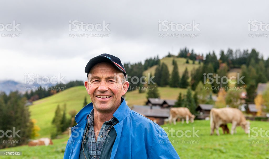 Portrait Of Dairy Farmer In Field With Cattle stock photo