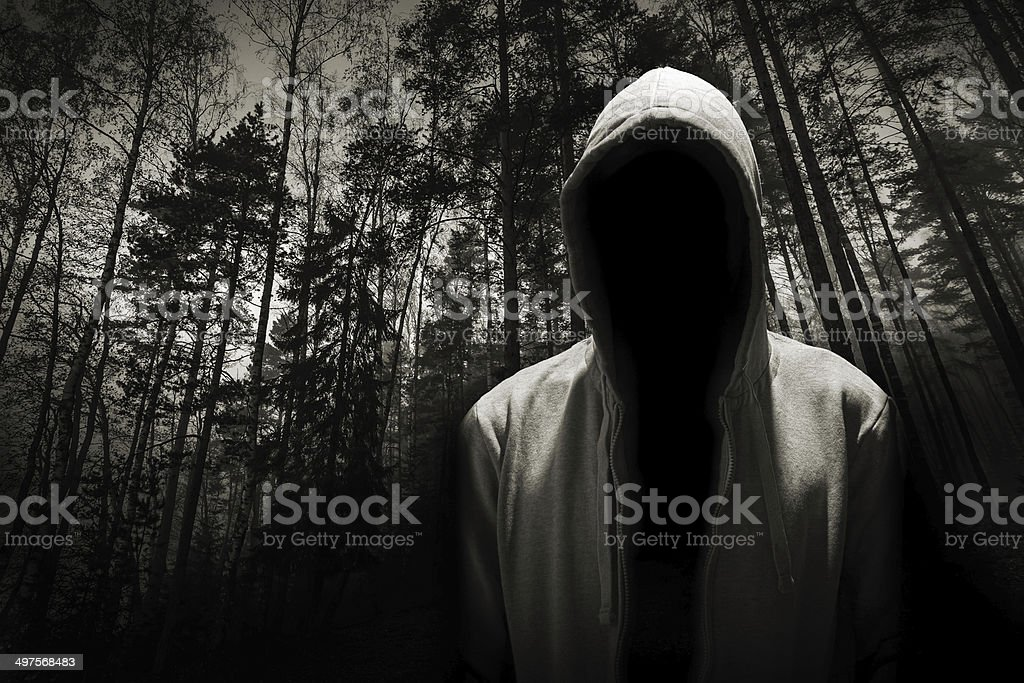 Portrait of dangerous man under the hood in the forest stock photo
