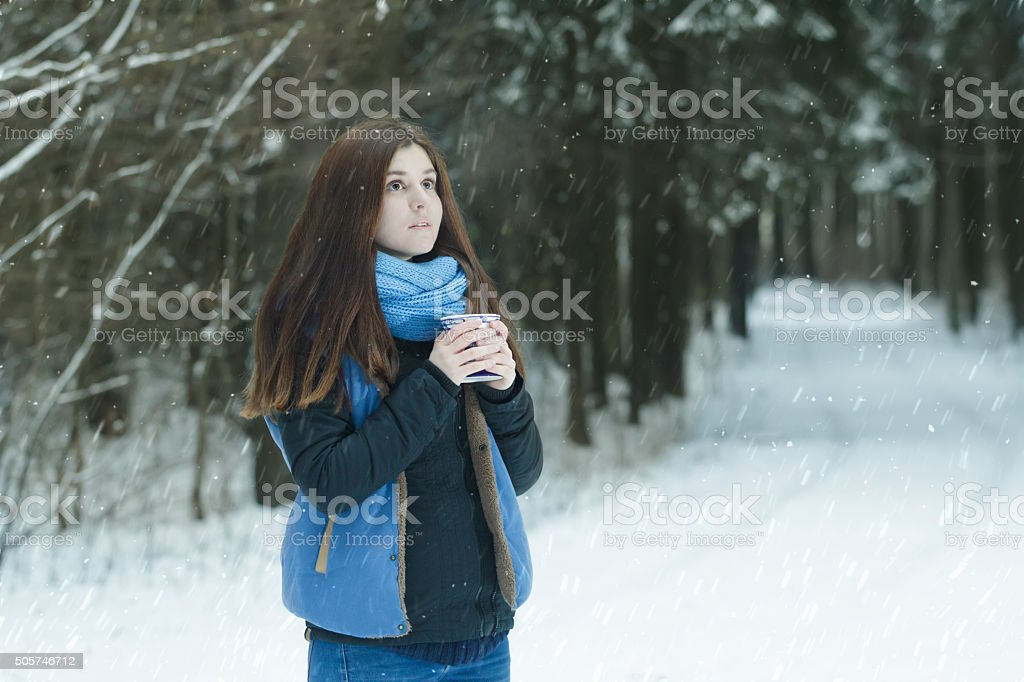 Portrait of daydreaming young lady holding cup with hot drink stock photo