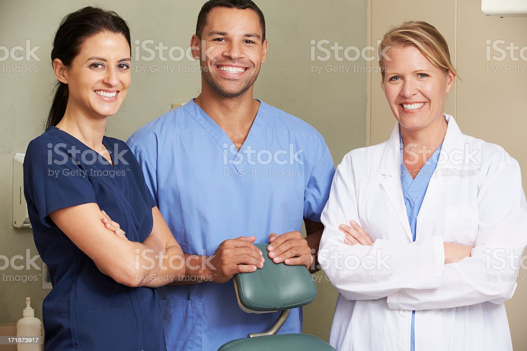 Portrait Of Dentist And Dental Nurses In Surgery stock photo
