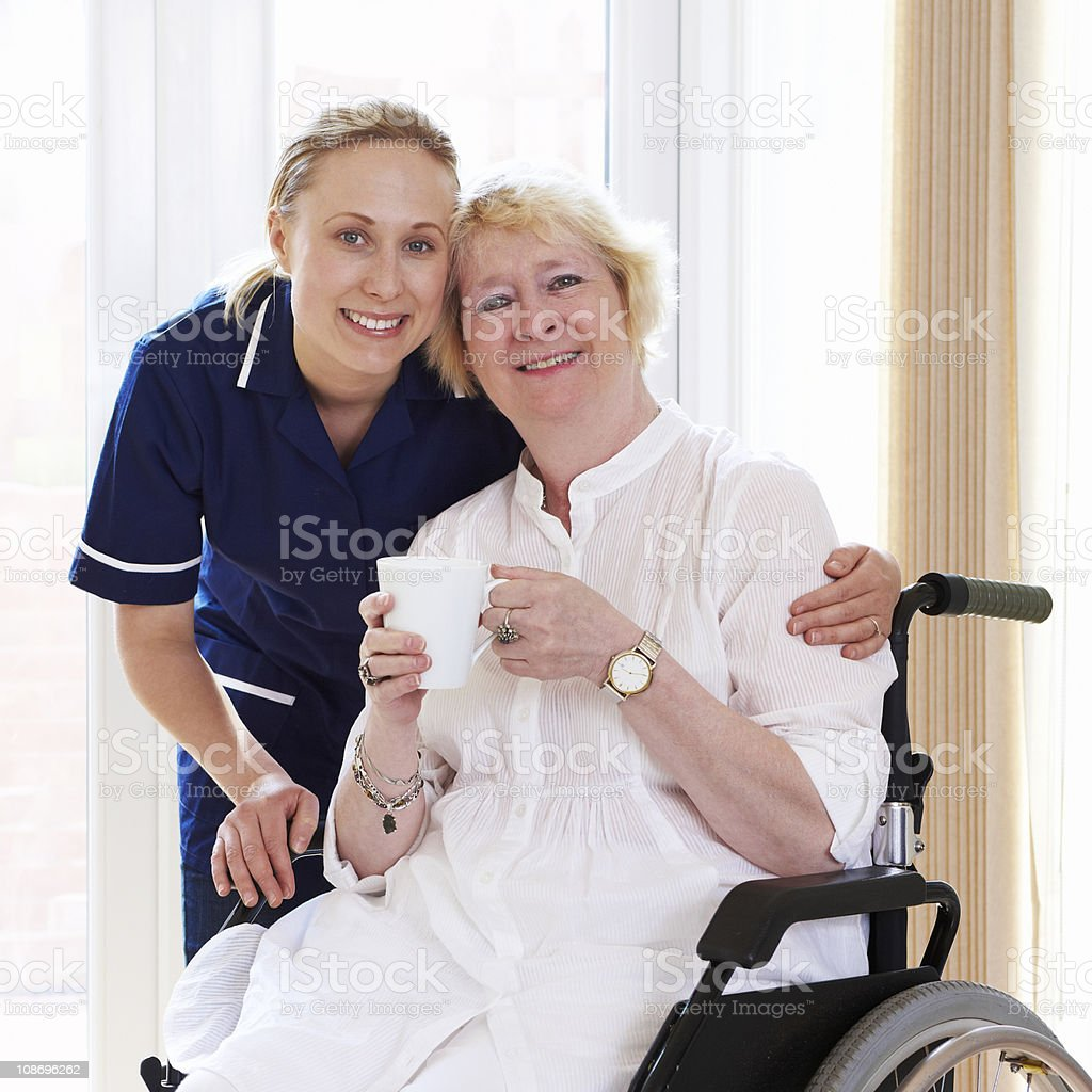 portrait of disabled woman in wheelchair with nurse royalty-free stock photo
