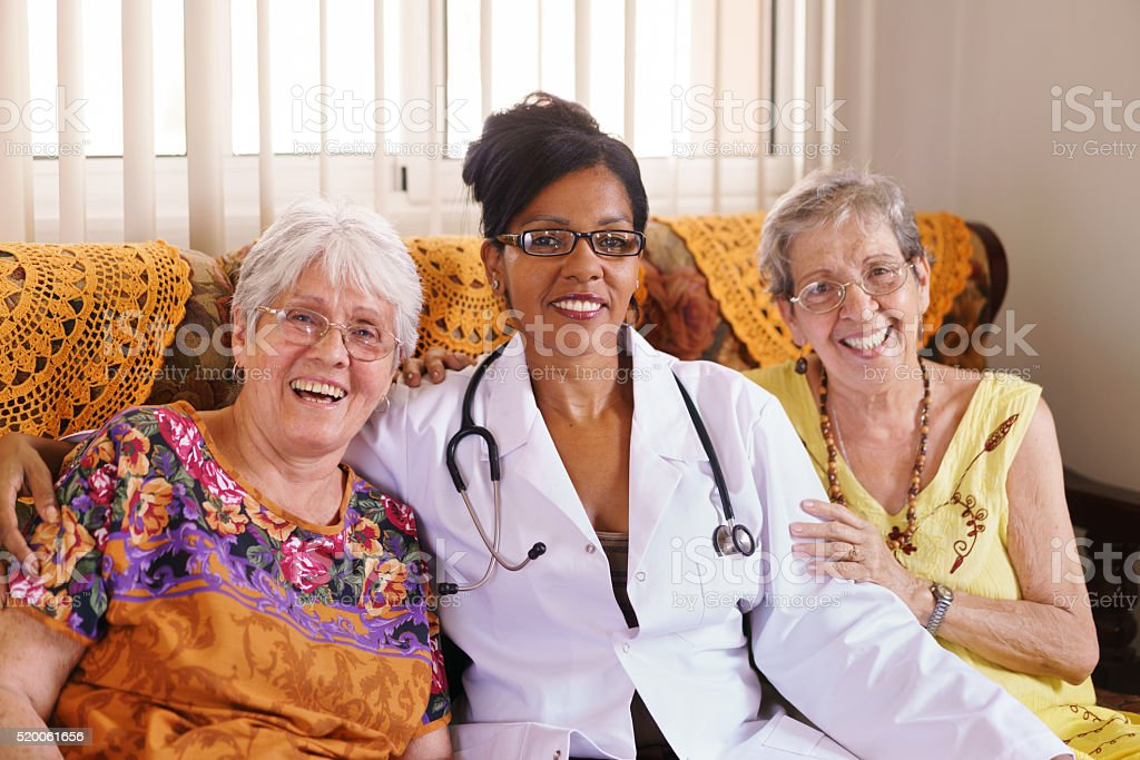 Portrait Of Doctor And Happy Old People In Hospice stock photo