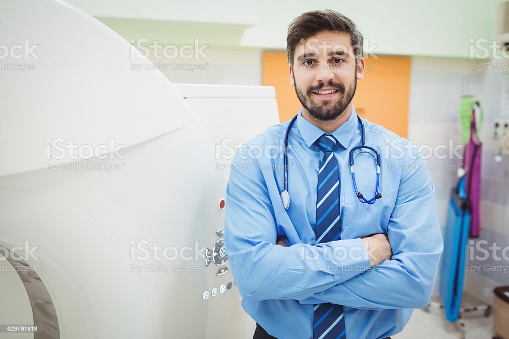 Portrait of doctor standing near mri scanner stock photo