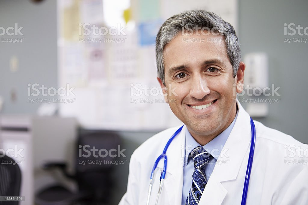 Portrait Of Doctor Working At Nurses Station stock photo