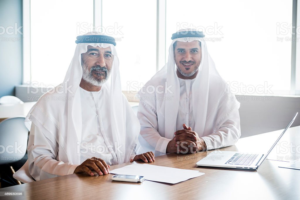 Portrait of two Arab Emirati businessmen at work in their office in...