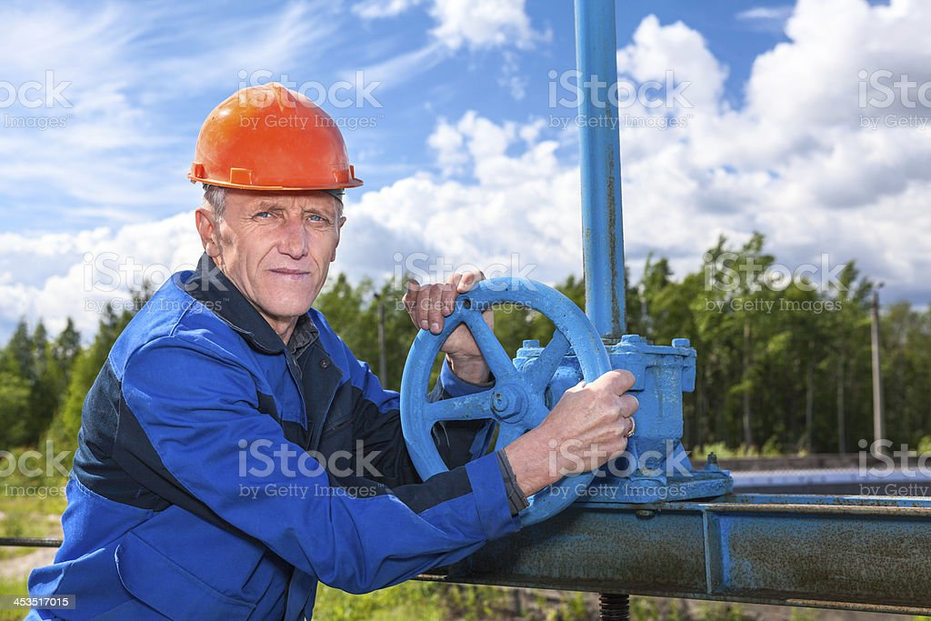 Portrait of elderly engineer in working uniform with pipe valve royalty-free stock photo