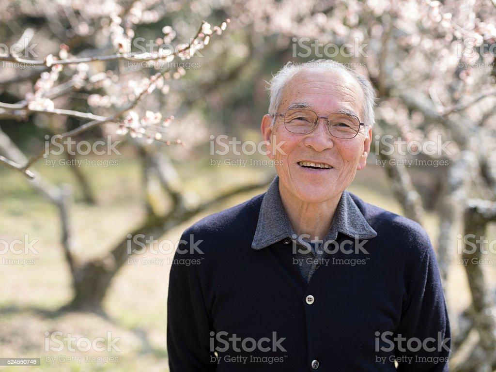 Portrait of elderly man in his 70s at Japanese shrine. stock photo