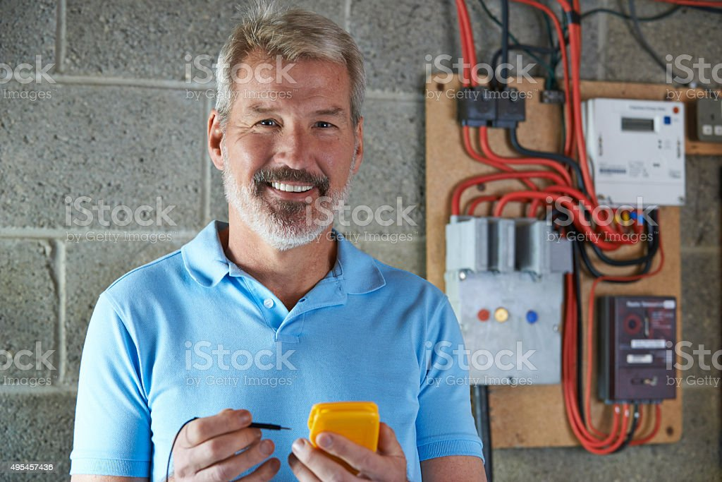 Portrait Of Electrician Standing Next To Fuseboard stock photo