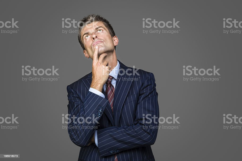 Portrait of elegant pensive businessman looks up looking for answers royalty-free stock photo