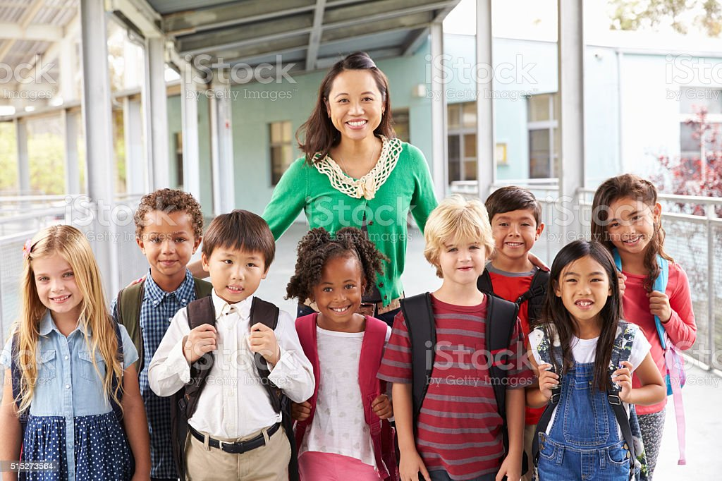 Portrait of elementary school kids and teacher in corridor stock photo