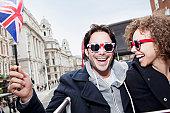 Portrait of exuberant couple with British flag and sunglasses riding double decker bus