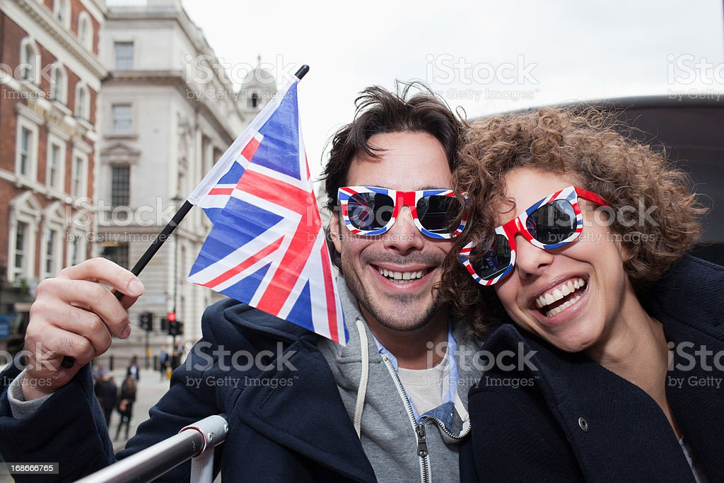 Portrait of exuberant couple with British flag and sunglasses riding double decker bus royalty-free stock photo