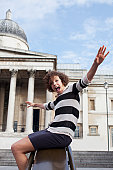 Portrait of exuberant woman with arms outstretched sliding on railing in front of historical landmark