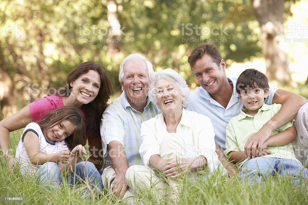 Portrait of family group sitting in a park stock photo