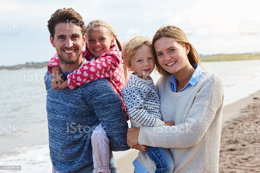 Portrait Of Family On Beach Vacation Walking By Sea stock photo