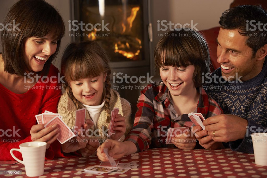 Portrait Of Family Playing Cards By Cosy Log Fire royalty-free stock photo