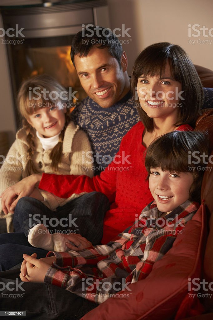 Portrait Of Family Relaxing On Sofa By Cosy Log Fire stock photo