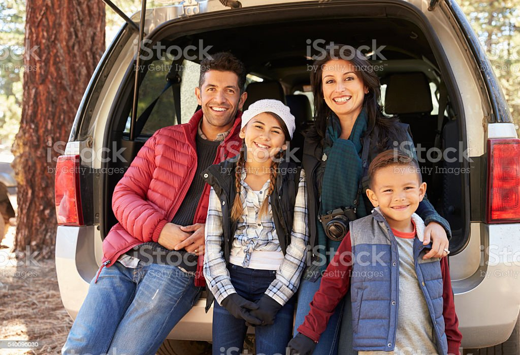 Portrait of family sitting in open back of car before stock photo