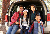 Portrait of family sitting in open back of car before
