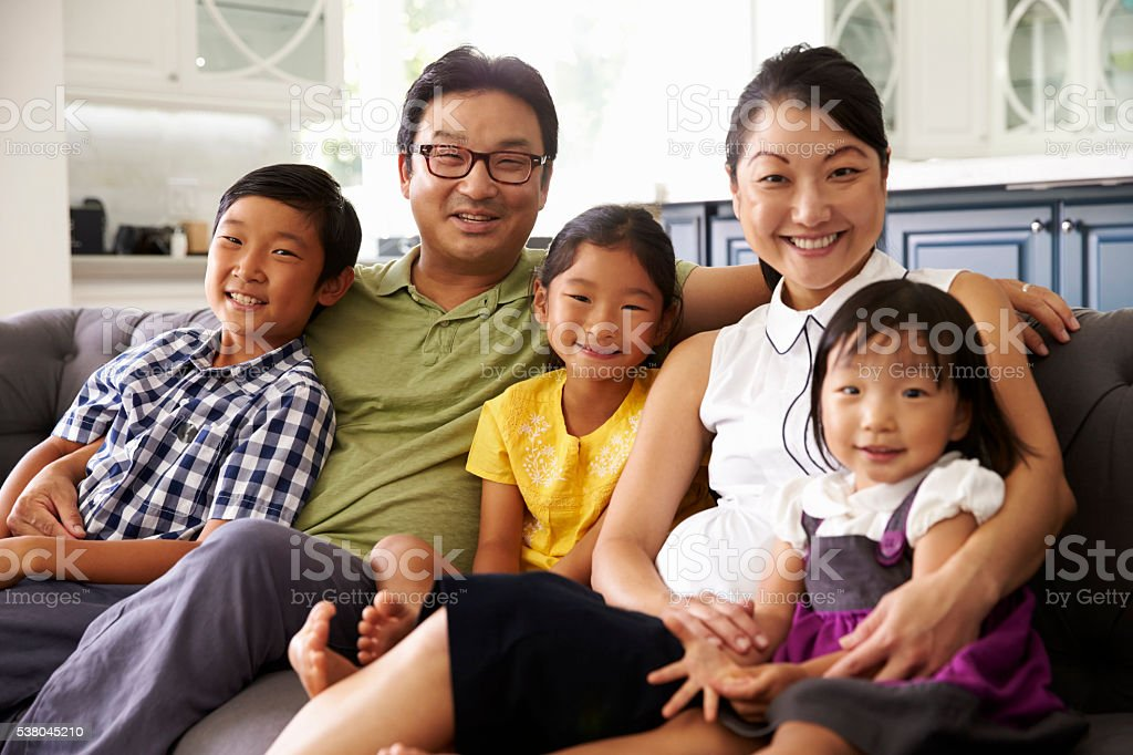 Portrait Of Family Sitting On Sofa At Home Together stock photo