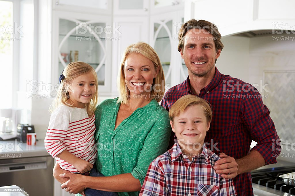 Portrait Of Family Standing In Kitchen Together stock photo