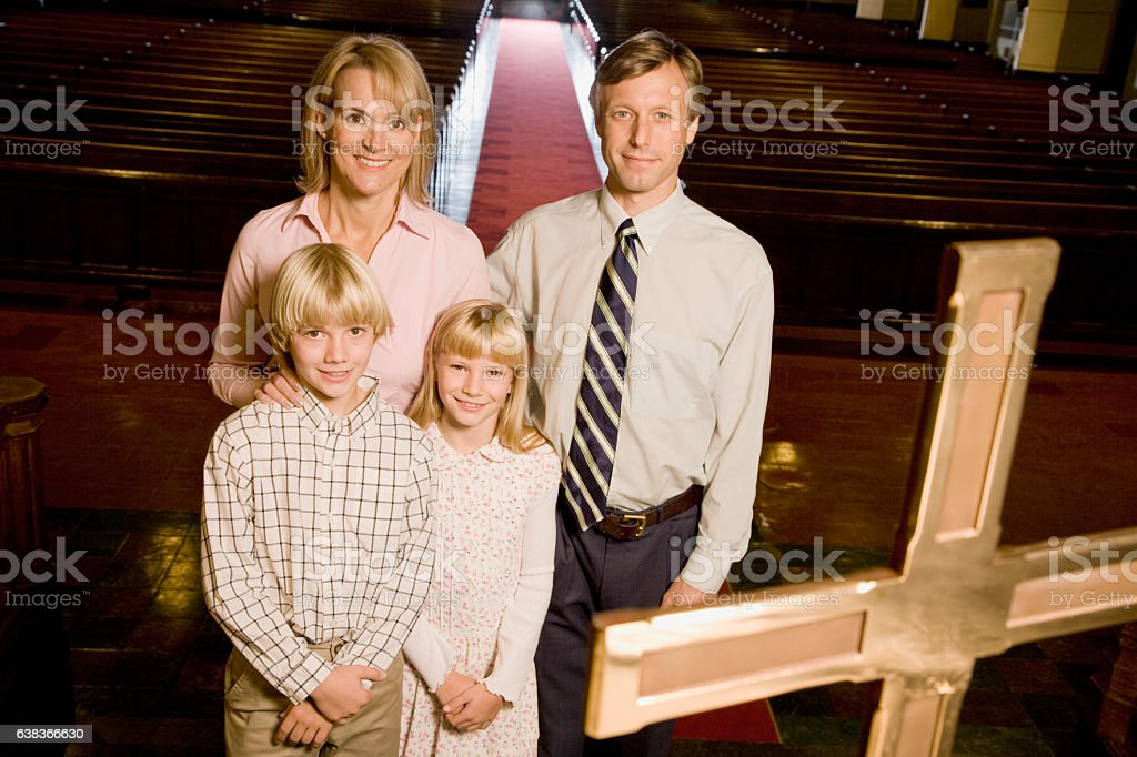 Portrait of family standing on altar in church stock photo