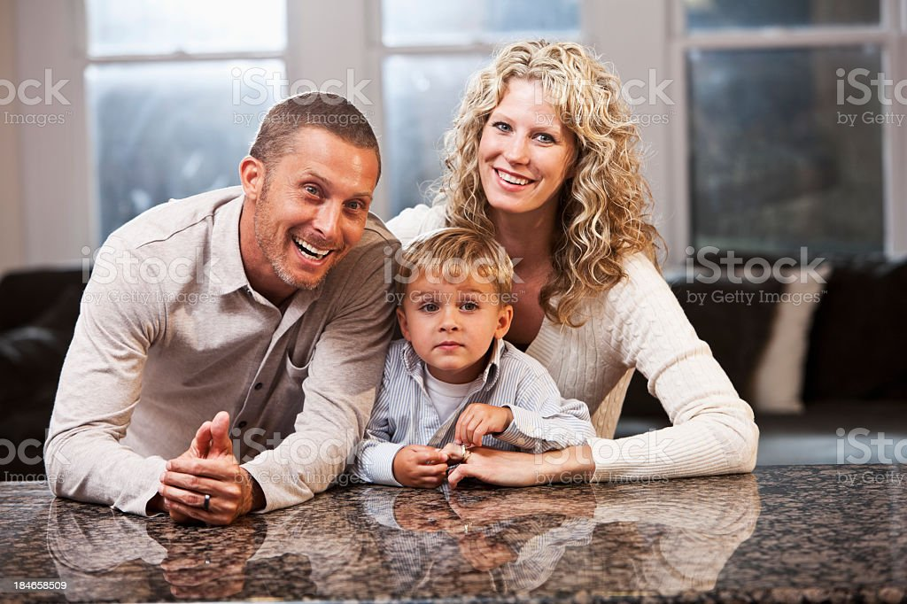 Portrait of family with little boy at kitchen counter stock photo